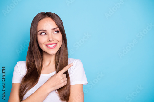 Fototapeta Close up photo of lovely youth pointing at copy space looking smiling wearing white t-shirt isolated over blue background obraz