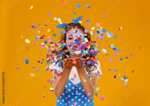 Obraz cheerful funny young woman with festive confetti on yellow . - fototapety do salonu