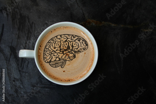 Fényképezés white cup with cappuccino and foam in the form of a silhouette of the brain on a