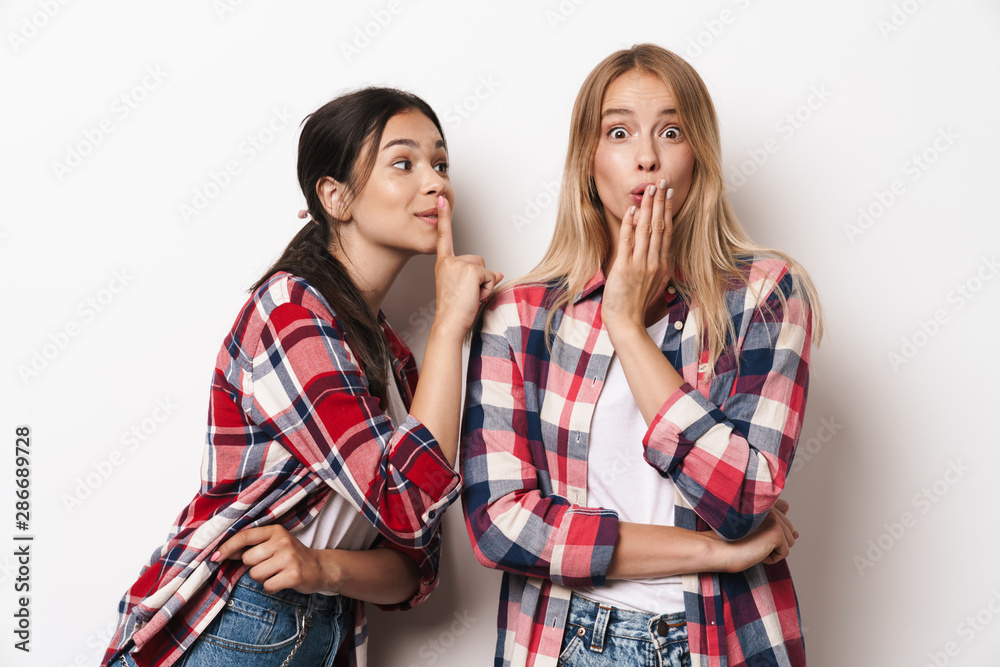 Fototapety, obrazy: Shocked young girls friends sisters posing isolated over white wall background.