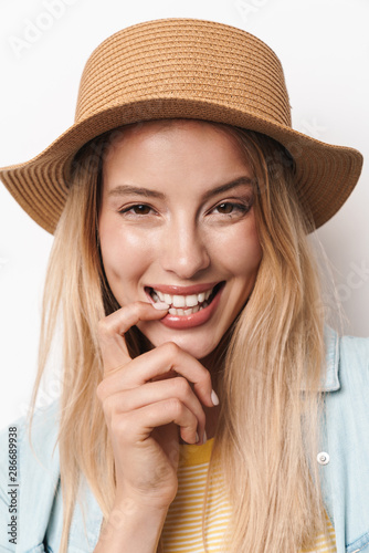 Happy smiling optimistic young pretty woman wearing hat posing isolated over white wall background.