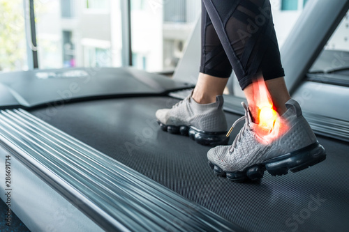 Woman on a treadmill with a painful injury on the ankle - 286691714