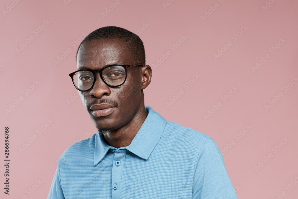 Fototapeta Portrait of African handsome guy in eyeglasses and in casual clothing looking at camera over pink background