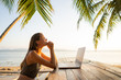 canvas print picture - freelancer girl with a computer among tropical palm trees work on the island in sunset