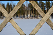 Criss Cross Pattern Of A Bridge's Fence With Forest And Frozen Lake In The Background.