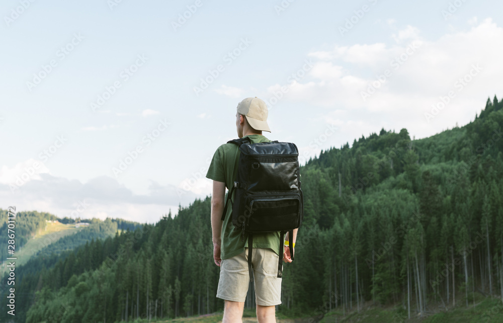 Fototapety, obrazy: Back view of young male traveler wearing cap with backpack standing alone in summer woods and looking at the mountain hills. Tourist guy enjoying the coniferous forest scenery and mountain landscape.
