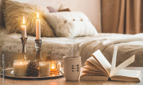 Poster Spa Book, cup of coffee and many candles on the home background. Home and home decor. Candles flame. HOME concept
