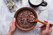 Hand Holding Spoon With Chocolate Cereal Balls. Healthy Breakfast And Diet Concept. Top View.