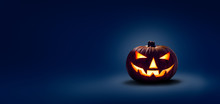 A Halloween Lit Jack O Lantern In A Spotlight Glow On A Wide Dark Blue Background