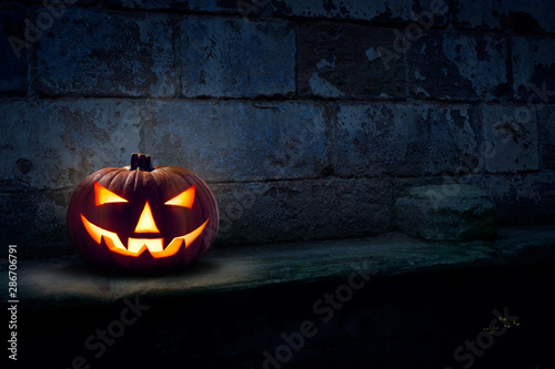 Photo A single scary evil looking halloween Jack O Lantern on the left side of a dark blue stone plinth background of a haunted castle at night