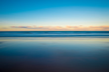 Scenic View Of The Glassy Smooth Shore Of A Deserted Beach During The Magic Hour Of Sunset