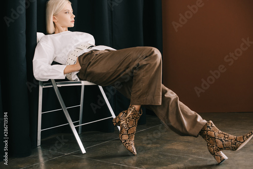 Fotomural  stylish blonde woman in white blouse and boots with snakeskin print sitting on c