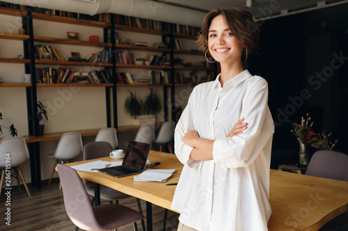 Obraz Young cheerful woman in white shirt happily looking in camera with desk on background in office - fototapety do salonu