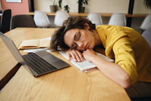 Young Tired Woman In Eyeglasses Asleep On Desk With Laptop And Notepad Under Head At Workplace