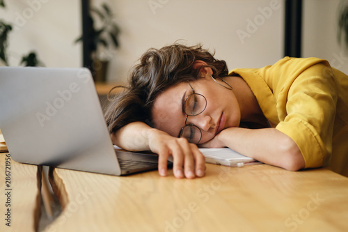 Young tired woman in eyeglasses sleeping on desk with laptop at workplace alone Wallpaper Mural
