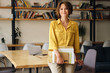 canvas print picture - Young beautiful woman in yellow shirt leaning on desk with notepad and papers in hand while happily looking in camera in modern office