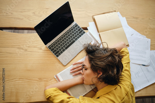 Photo Top view of young tired woman asleep on desk with laptop and documents under hea