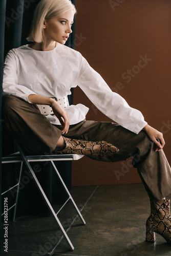 stylish blonde woman in white blouse and boots with snakeskin print sitting on chair near curtain on brown