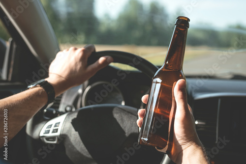 Driver is driving a car with a bottle of beer in hand Canvas Print