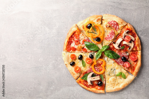 La pose en embrasure Pizzeria Delicious pizza with different pieces on grey background, space for text