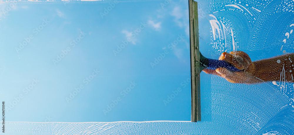 Fototapeta Fensterputzer putzt Fenster mit Schaum und Abzieher Panorama