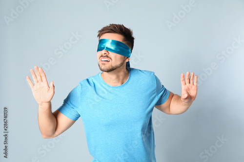 Young man with light blue blindfold on grey background Wallpaper Mural