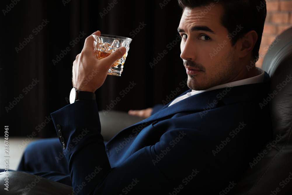 Fototapeta Young man with glass of whiskey indoors