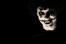 The Terrible Creepy Clown In A Black Wig Grins, Looking At The Camera. Empty Space On The Left, Black Background.