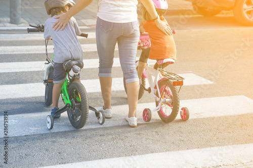 Fotografia, Obraz  Mother goes pedestrian crossing with children on bicycles
