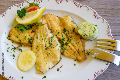Tablou Canvas fried plaice fillet with herb butter and lemon on a plate, typical food in north