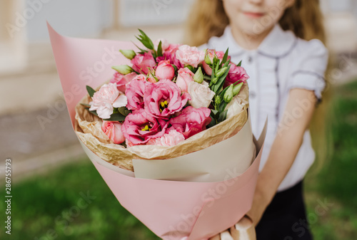 Valokuva School girl dressed in school uniform holding a bright pink festive bouquet of beautiful flowers for teacher