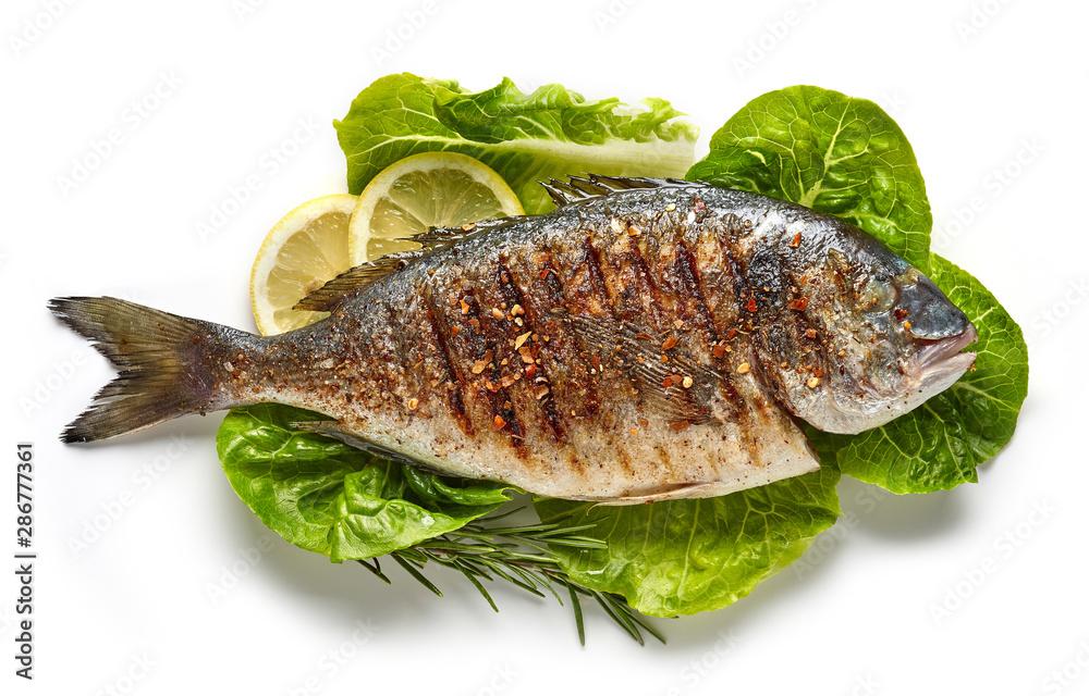 Fototapeta grilled fish on green salad leaves