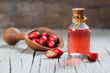 Glass Bottle Of Rosehip Seed Essential Oil With Fresh Rose Hip Fruits In Shovel On Wooden Rustic Background. Dogrose Oil With Fresh Dog Roses