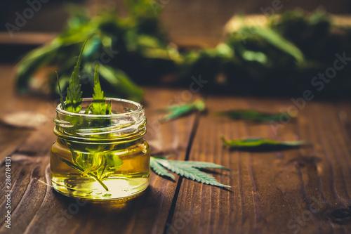 Fototapeta Glass jar with hemp oil and fresh leaves on wooden background obraz