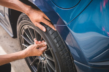 Closeup Male Automotive Technician Removing Tire Valve Nitrogen Cap For Tire Inflation Service At Garage Or Gas Station. Car Annual Maintenance And Repair Concept. Safety Road Trip And Travel Theme.