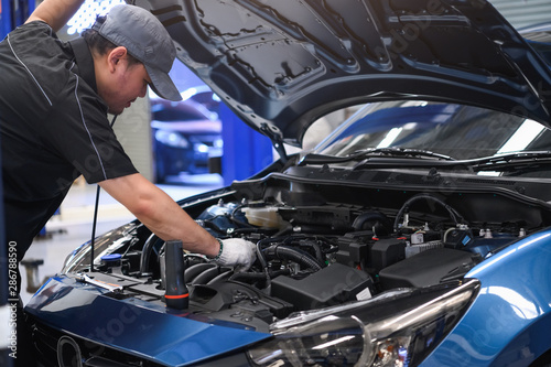 Fotomural Asian male auto mechanic examine car engine breakdown problem in front of automotive vehicle car hood