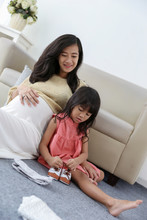 Asian Girl Is Fixing The Baby's Shoelaces With Her Pregnant Mother When Sitting On The Floor