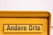 Gelber Briefkasten mit Aufschrift Andere Orte lädt zur analogen Kommunikation per Brief und Einschreiben ein und lässt den Job des Briefträgers nicht aussterben