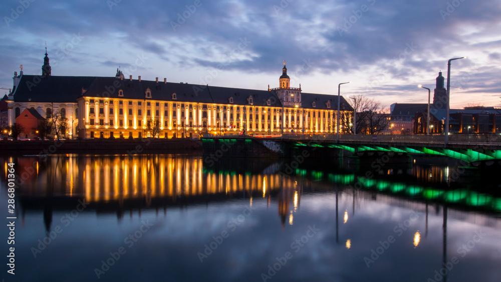 Odra i Uniwersytet Wrocławski na tle pięknego wieczornego nieba z chmurami.