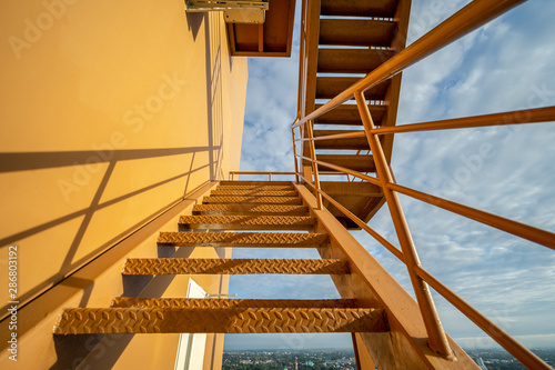 Fotografie, Obraz Fire escape stairs mounted to the outside, Emergency exit with yellow wall