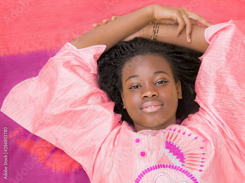 Fotografía Portrait of a beautiful girl wearing a celebration clothing and lying on a loinc
