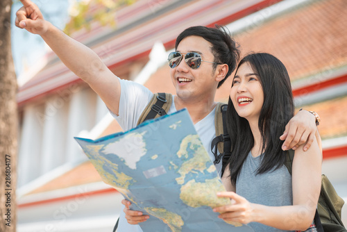 Traveler Asian couple direction on location map in Bangkok, Thailand, sweet Asia couple looking on map find landmark while spending holiday trip Canvas Print