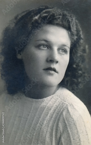 Photo Vintage 1940´s vintage glamour photo of a young woman with thick curly hair, wearing a white knitted sweater looking sideways