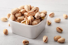 Salty Food, Healthy Eating, Nutritious Meal And Protein Rich Snack Conceptual Idea With Close Up Pistachio Nut Porcelain Bowl And Many Scattered Falling Nuts On Rustic White Wood Table