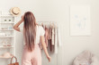 canvas print picture Young woman choosing clothes in her dressing room, back view