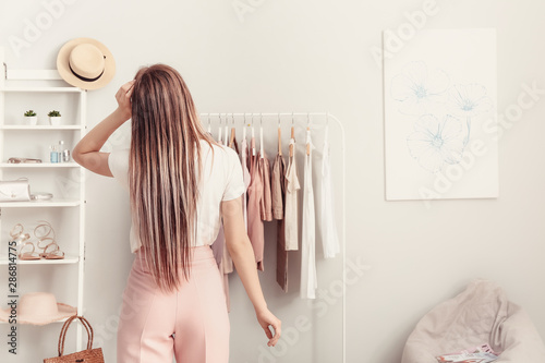 Fotografiet  Young woman choosing clothes in her dressing room, back view