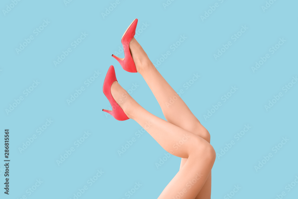 Fototapeta Legs of young woman in high-heeled shoes on color background