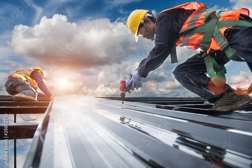 worker builder with hand drill at metal profile roof installation Metal roof con Fototapeta