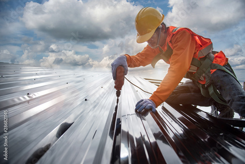 Fotografía  worker builder with hand drill at metal profile roof installation Metal roof con