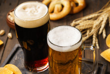 Two Glasses Of Beer - Light And Dark With Various Snacks.